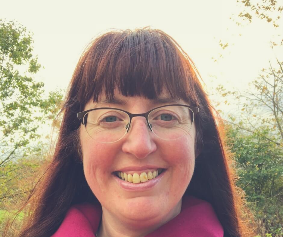 "A woman (Morgan Prince) looks straight into the camera smiling. She has red hair and blue eyes. She wears glasses with a rimless frame on the bottom. Wrinkles spread out from the sides of her eyes and on her cheeks as she smiles. The sun is rising in the background behind lush green trees. Image for ""Things I've learned about myself since becoming a mother"""