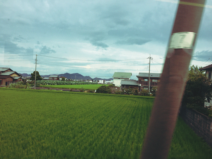 A glimpse of the Japanese countryside with its rolling green hills and short houses en route to Naoshima Island Japan