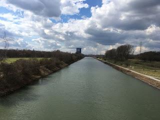 Blick über den Rhein-Herne-Kanal auf das Gasometer. An der linken Uferseite steht der tanzende Strommast namens Zauberlehrling