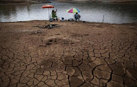 Men fish next to cracked ground as the Atibainha dam lake dries up due to a prolonged drought in Nazare Paulista, Sao Paulo state, October 17, 2014. (Credit: Reuters/Nacho Doce/Files) Click to Enlarge.