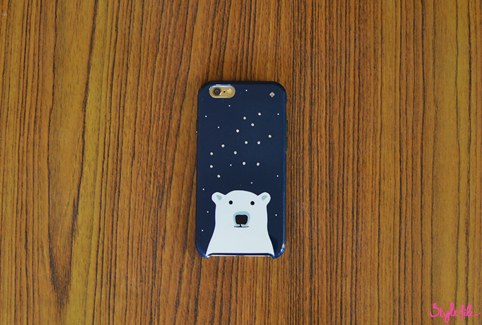 Flatlay image of Apple Iphone 6 mobile phone in a navy blue Kate Spade phone cover with a polar bear on a table