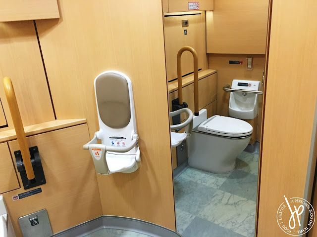 large train restroom with toilet, child seat, and full length mirror