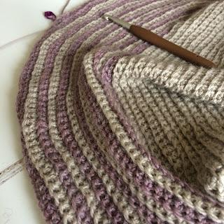 Close up of crochet shawl using grey and purple yarn