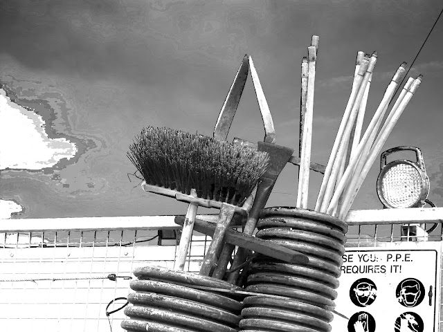 Broom and other workers' implements on back of lorry - black and white