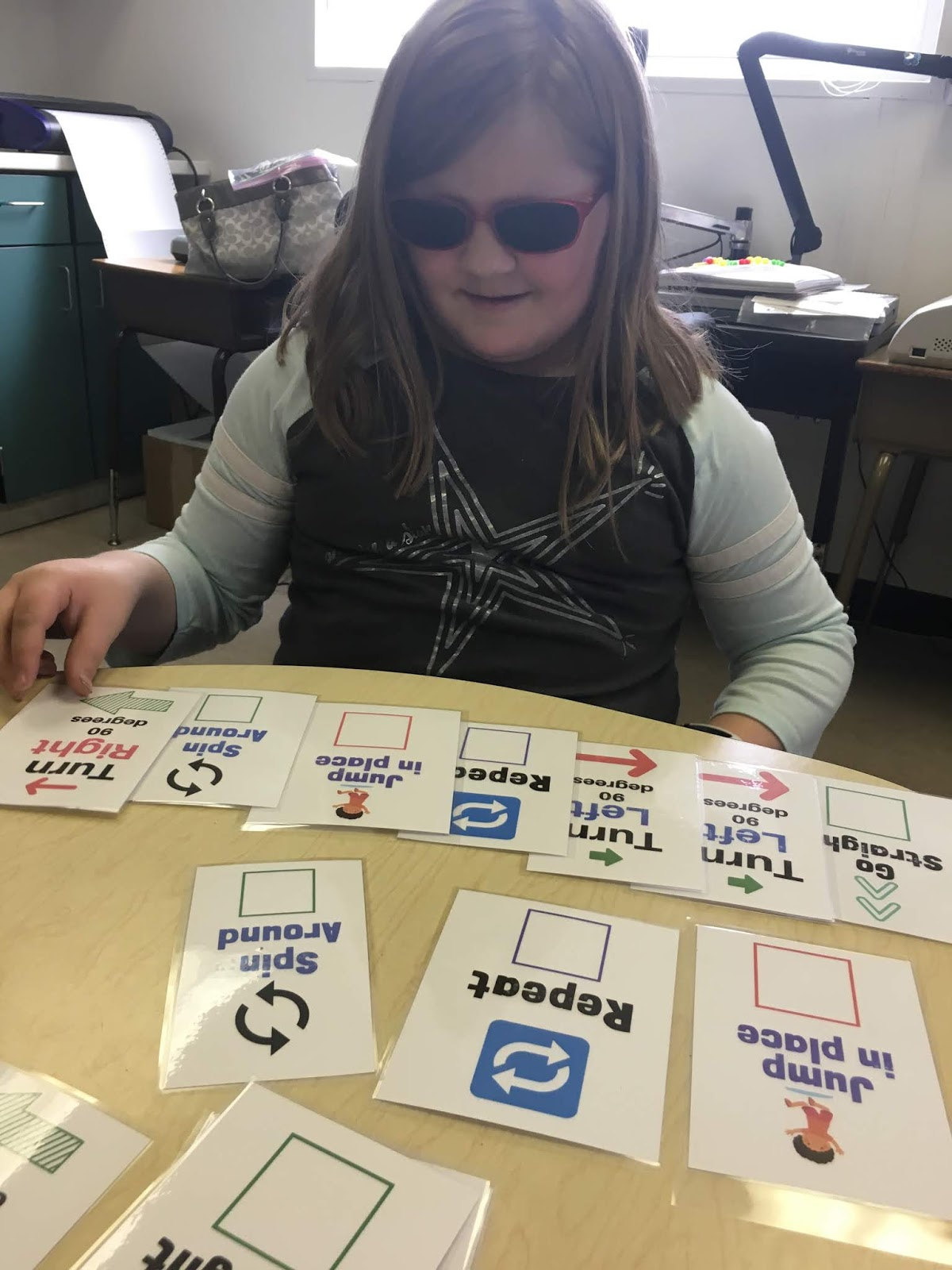 A female student arranges the cards into a line of code