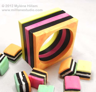 Yellow, black, pink, black and orange square bangle stack look like layers of a licorice allsort.