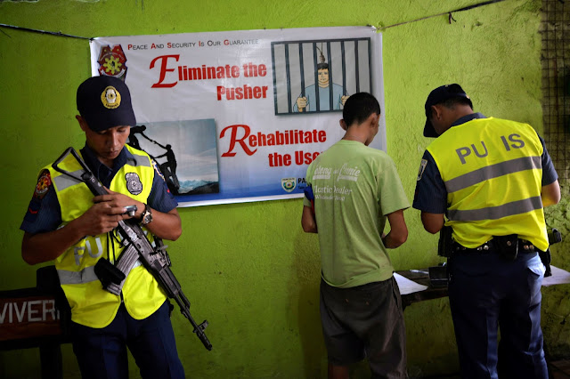 Image Attribute: A policeman interviews a drug user who voluntarily surrendered to local authorities in Pasig city, metro Manila, Philippines September 17, 2016. Picture taken September 17, 2016.   REUTERS/Ezra Acayan