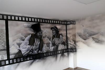Artystyczne malowanie ściany w pokoju telewizyjnym, aranżacja sciany w sali telewizyjnejj poprzez malowanie, czarno-biały obraz namalowany na ścianie, motyw z filmu Janosik