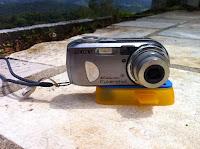 Camera com um suporte de plástico instalada na parte de baixo, como uma base.