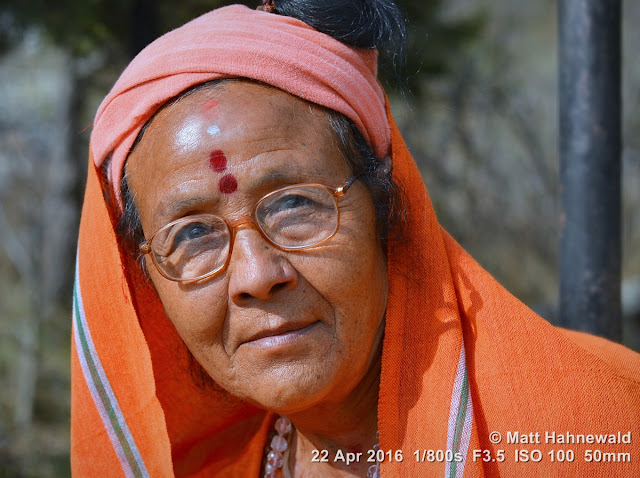 shakti peetha; red tilaka; female sadhu; holy woman; orange; Muktinath; Muktinath Temple; Hindu; eyeglasses; Matt Hahnewald Photography; Facing the World; photo; image; closeup; street portrait; headshot; outdoor; world cultures; cultural; one person; character; people; female; adult; ethnic; horizontal format; human; face; eyes; eye contact; photography; consent; empathy; rapport; portrait; portraiture; environmental portrait; ethnic portrait; travel portrait; travel destination; color; 4x3 aspect ratio; posing; Mustang District; Asia; South Asia; Nepal; Himalayas; Annapurna Circuit; Nikon D3100; Nikkor AF-S 50mm f/1.8G; trekking; colourful; incredible; religion; Hinduism; shawl; headcovering