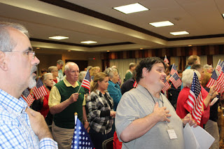 Top Dog attendees saying the Pledge of Allegiance, each holding a personal-sized American Flag