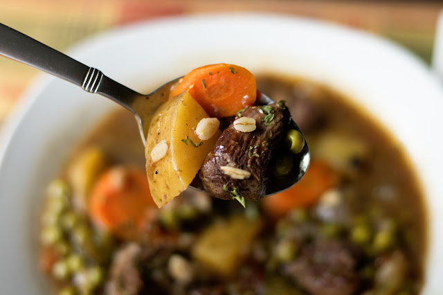 A spoonful of the beef and barley stew.
