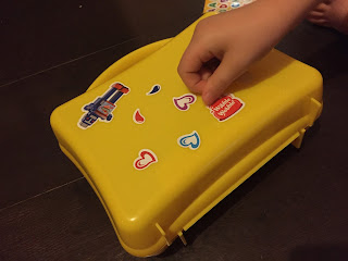 A yellow Hartley's lunchbox being decorated with stickers by a child's hand