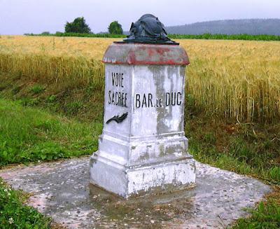 Monolito de piedra en primer plano, en segundo un campo de trigo. En el monolito se lee: Voie Sacrée. Bar le Duc