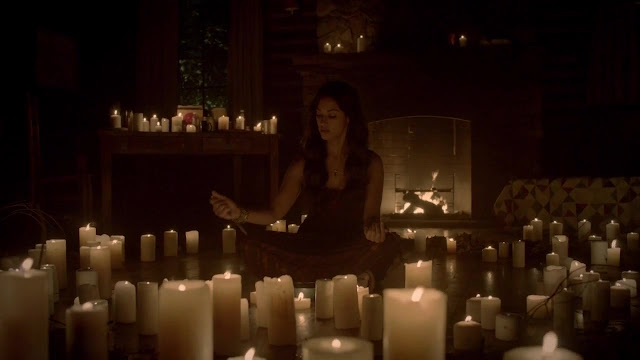 Screenshot of a witch from The Vampire Diares surrounded by at least fifty white pillar candles.