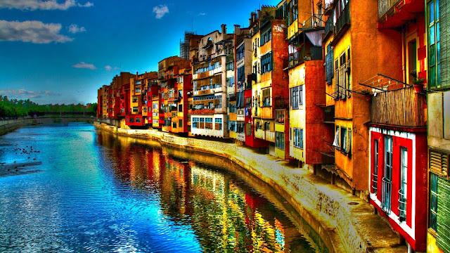 HD wallpaper met Italiaans dorpje aan het water van een rivier.