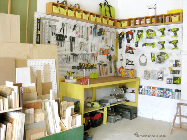 Ryobi tools on pegboard with yellow bench and scrap wood holder in garage
