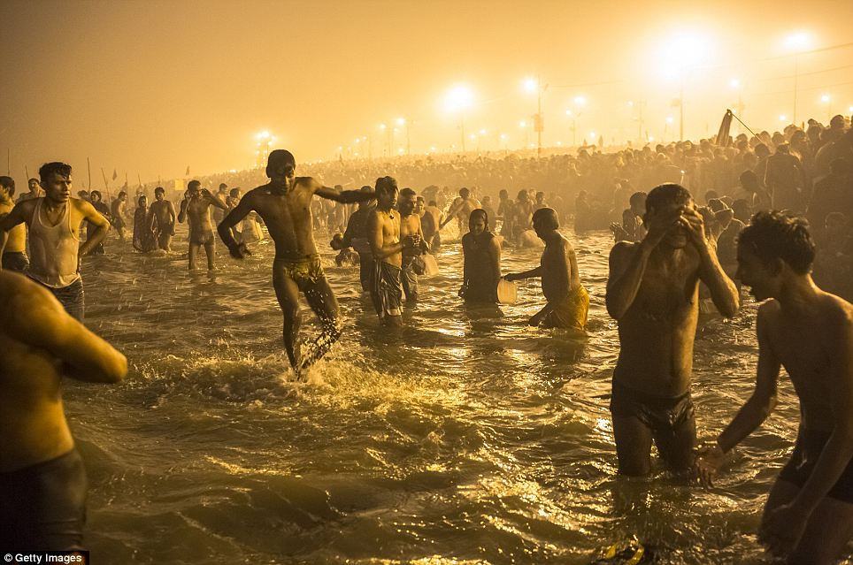 Holy men pictured bathing in rivers during Hindu