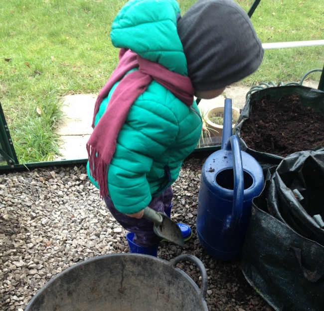 toddler looking into bag of compost