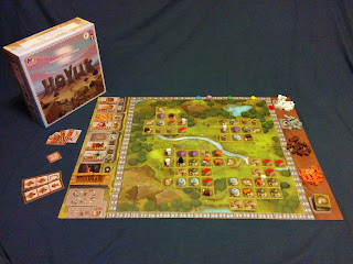 The game box next to the board set up as if in the middle of a game. The box art shows large stone letters spelling out the title, Hoyuk, standing in a desert landscape against a sun preparing to set. The board shows a valley with stone outcroppings, trees, a river, and a pond. Tiles representing houses and pens are placed about the board, with meeples representing ovens, shrines, villagers, and cattle on some of them. Supplies of meeples are grouped on the right edge of the board, with various cards and building tiles on the left edge.