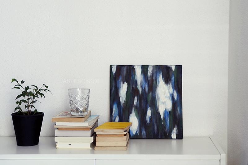 Dekoration mit selbstgemaltem abstrakten Bild in Blau-/ Grüntönen, Zimmerpflanze, Bücherstapeln und Teelicht