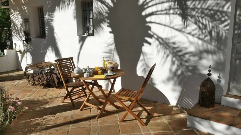 mesa con desayuno en patio de antiguo cortijo en Córdoba