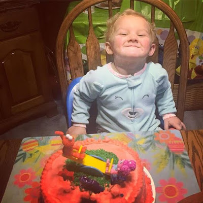 Grand baby with her cake (making a funny face) -Vickie's Kitchen and Garden