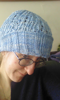A woman wearing a cable and lace beanie hat, knit in light blue yarn.