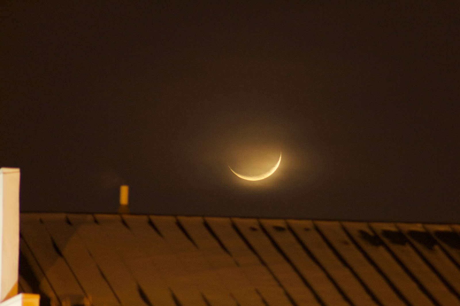 crescent moon over building roof