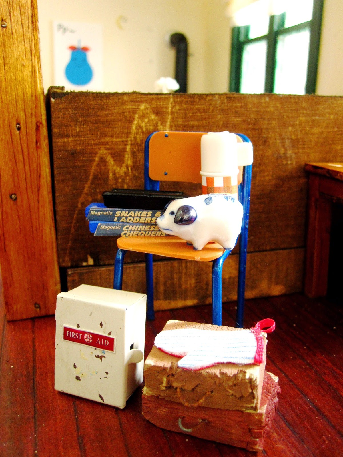 Selection of modern dolls house miniatures including a school chair with blue legs, an old first aid cupboard, two school cases, games of snakes and ladders and checkers, a blue and white piggy bank and a red checked flask.