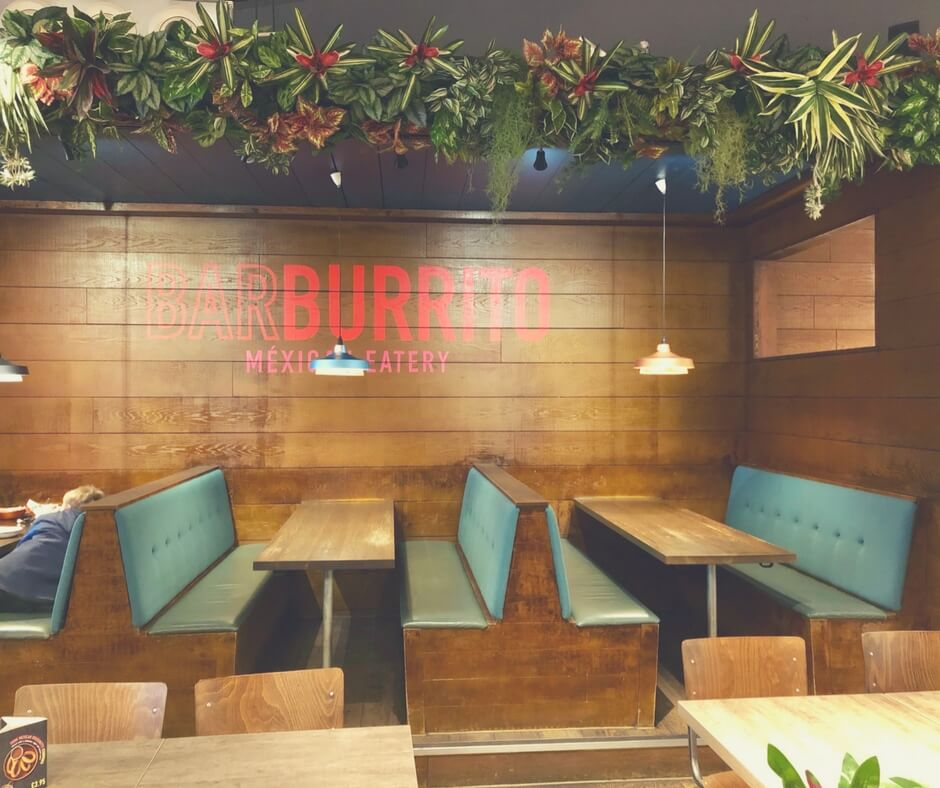 Barburrito, Nottingham. The booths next to the wall have green soft seats and brown tables. A colourful garland sits close to the ceiling. Image for Easter lunch at Barburrito, Nottingham (and Giveaway!).