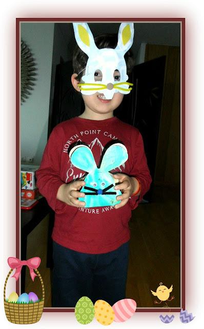 Foto do meu filho com máscara de coelho e segurando um caixa de cabeça de coelho da Páscoa, contendo ovinhos de chocolate