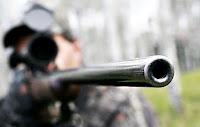 Bir avcı dürbünlü tüfeğiyle nişan alırken namlu ucunun önden görünüşü