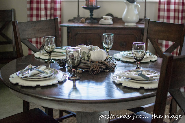 Vintage silverware and linens paired with brown transferware. And a nice centerpiece using natural items.