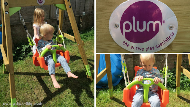 Plum Wooden Growing Swing Set; siblings playing together; Plum logo on cross bar and lap belt design