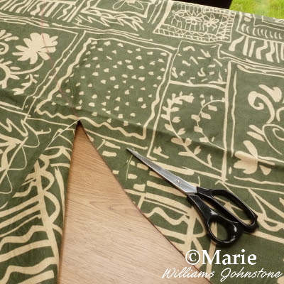 Cutting through the green patterned fabric