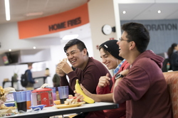 Students laugh over a meal in the dining hall