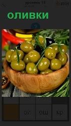 в чашке лежат оливки и вокруг разная зелень