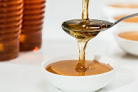 An image in which honey is being poured on a spoon placed over a bowl