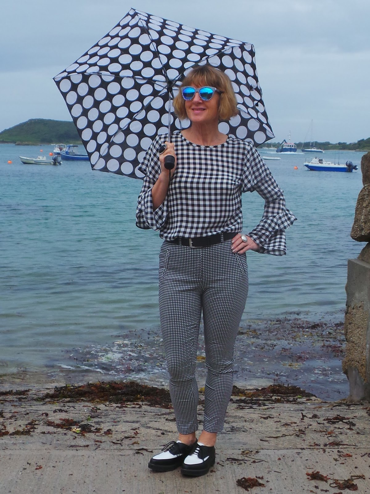 Showing how you can have fun with black and white and pattern mixing, Anna Parkes from Anna's Island Style in gingham, check trousers and a fun circles umbrella