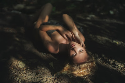 Linda chica rubia acostada en la arena mirando a cámara