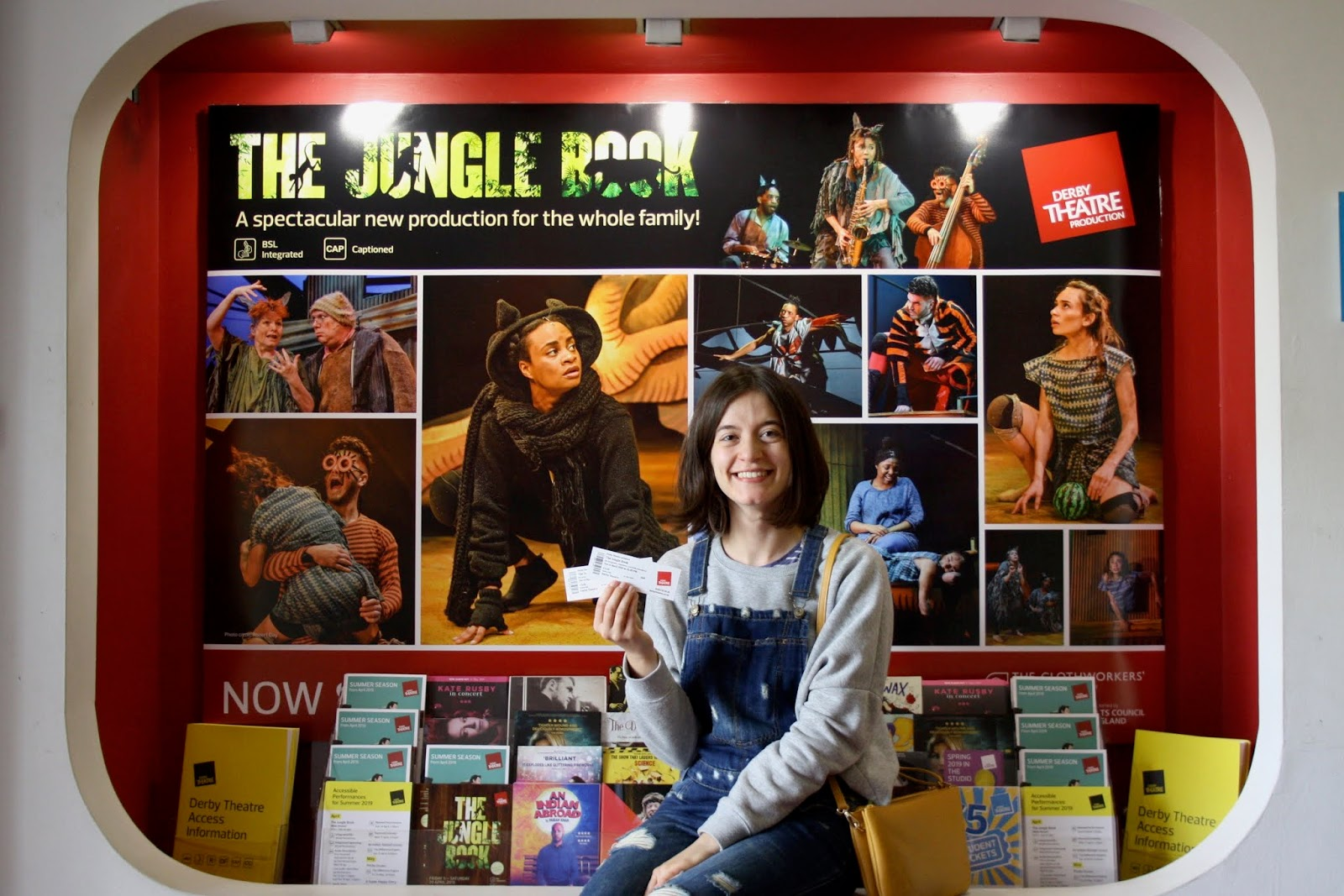Abbey holding her tickets to The Jungle Book, seated before a poster advertising the performance at Derby Theatre