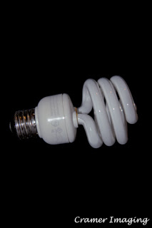 Photograph of a single compact fluorescent light bulb on its side on a black background by Cramer Imaging