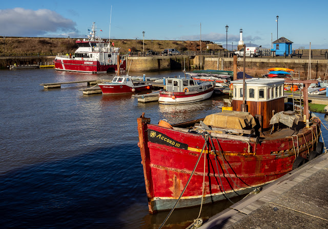 Photo of colour coordinated boats at Maryport Marina with MV Achiever in the distance