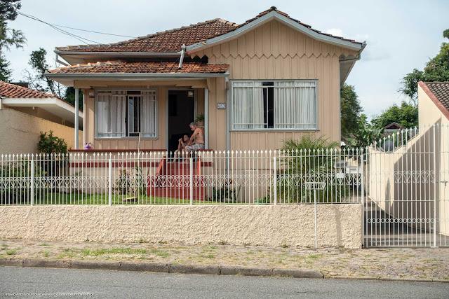 Casa de madeira na Rua Cláudio Manoel da Costa com duas pessoas na varanda