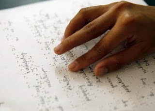 Fingers on a braille page, with ink writing along the braille letters