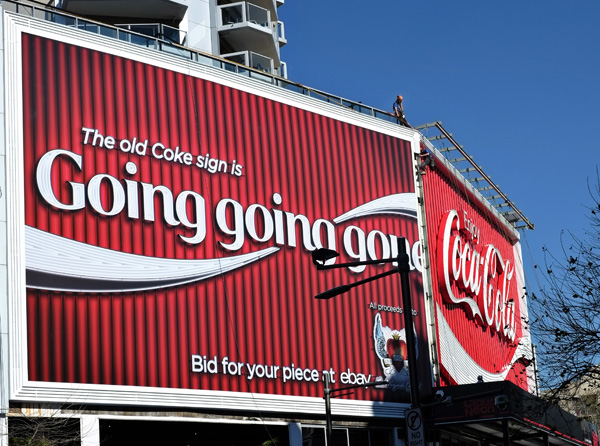 The new Coke sign in Kings Cross Sydney and the Wayside Chapel auction sign. Photo by Kent Johnson.