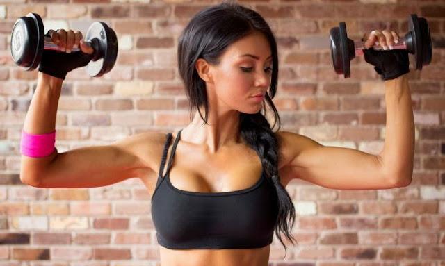 Chica fitness entrenando con pesas para evitar los pechos caídos