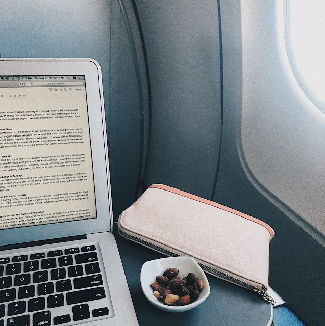 laptop with snack and makeup bag next to plane window