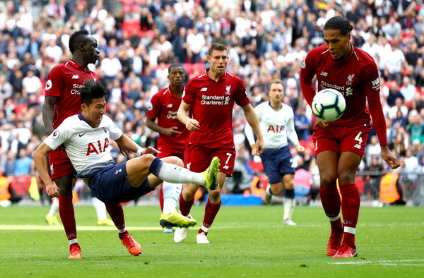 Tottenham forward Son battles for the ball against Liverpool's Saido Mane, Van Dijk